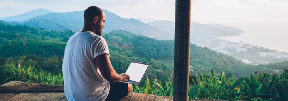 man with laptop working remotely with stunning view